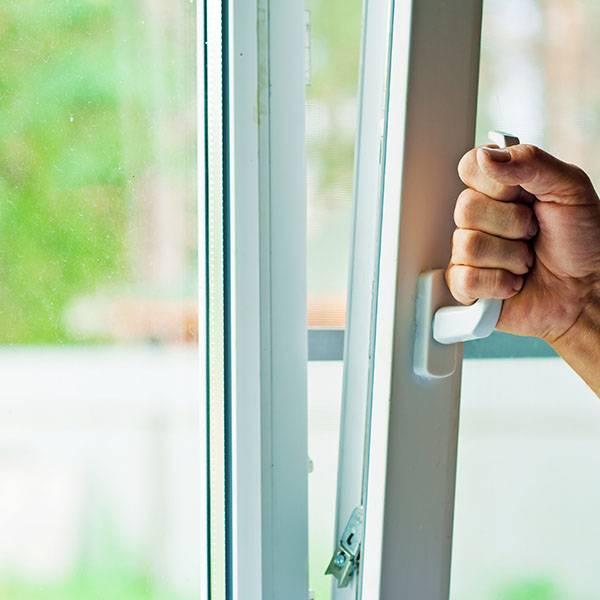 hand using handle to open window