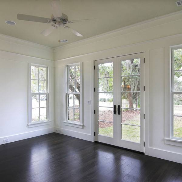 empty white room with ceiling fan and large windows