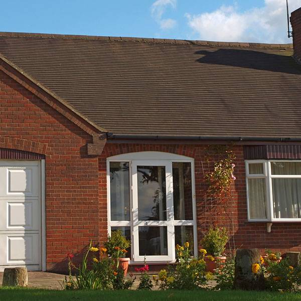 large red brick house with garage and upvc front door