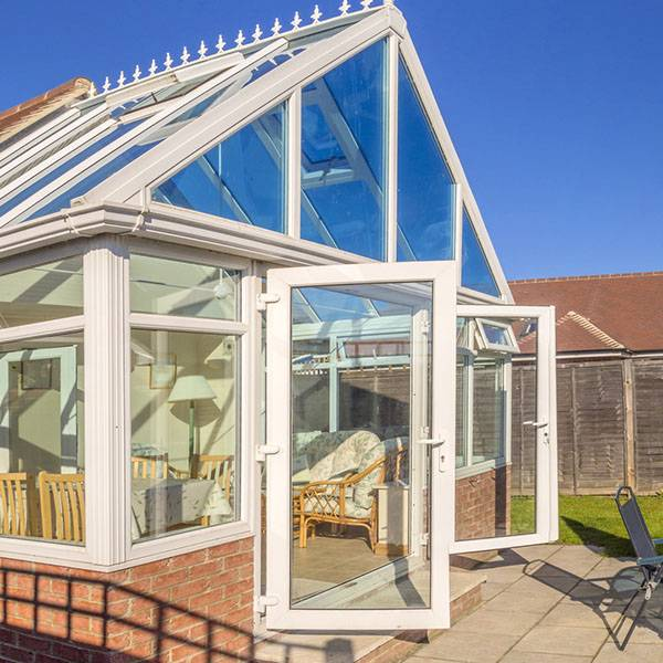 large conservatory with open upvc doors facing garden patio